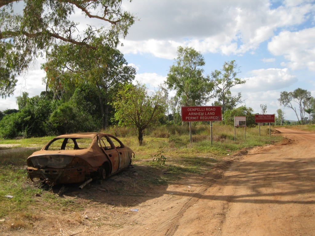 Burnt car and road signs at East Alligator River right at the border to Kakadu National Park on the Arnhem Land side