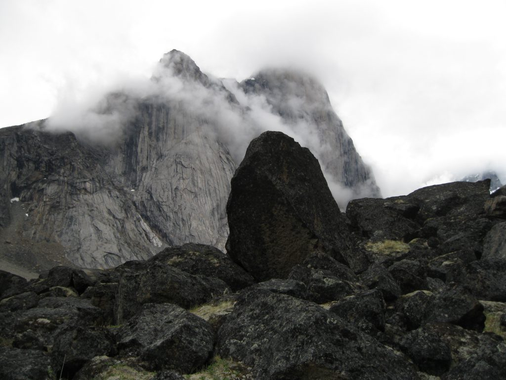 Mount Thor in the mist fronted by boulders
