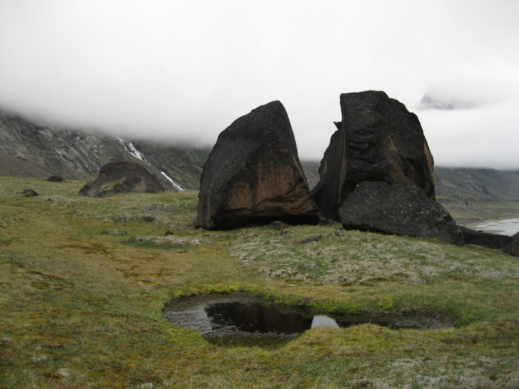 """Boulders at """"The Crib"""" fronted by a Pond and Schwarzenbach Falls in the mist in the background"""